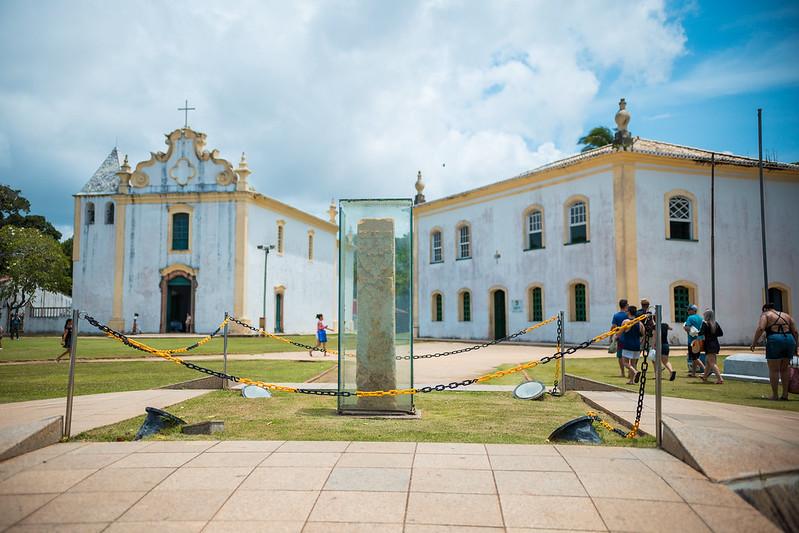 Construções antigas de cor amarela e branco com um monumento ao meio protegido por vidro no Centro Histórico de Porto Seguro na Bahia
