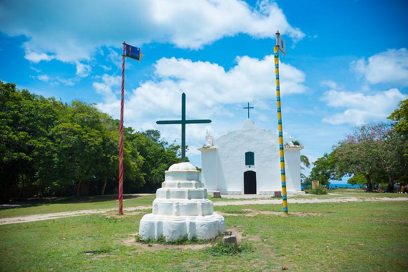 Quadrado em Trancoso próxima a Porto Seguro - Igreja pintada de branco atrás com uma cruz a frente.