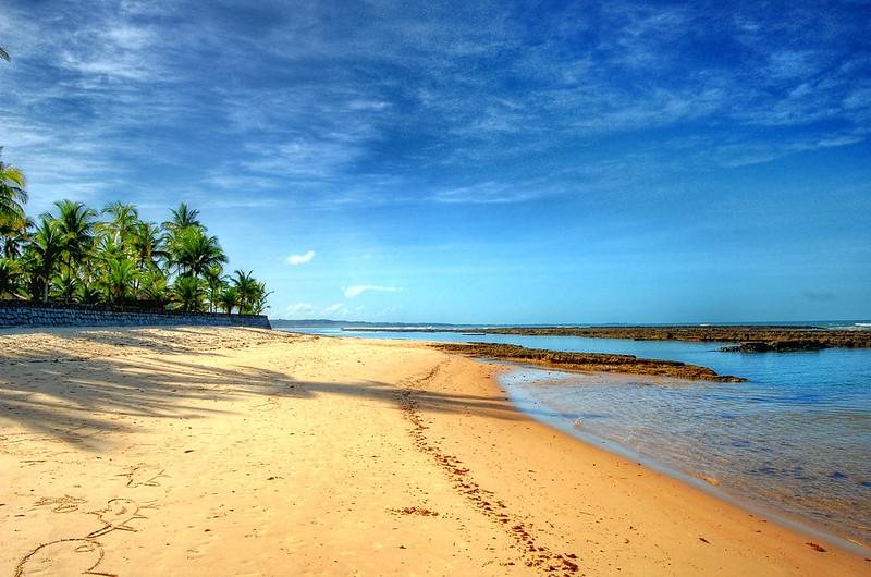 Praia com areia dourada, palmeiras na esquerda, mar com águas cristalinas e céu azul em Arraial d'Ajuda na Bahia.