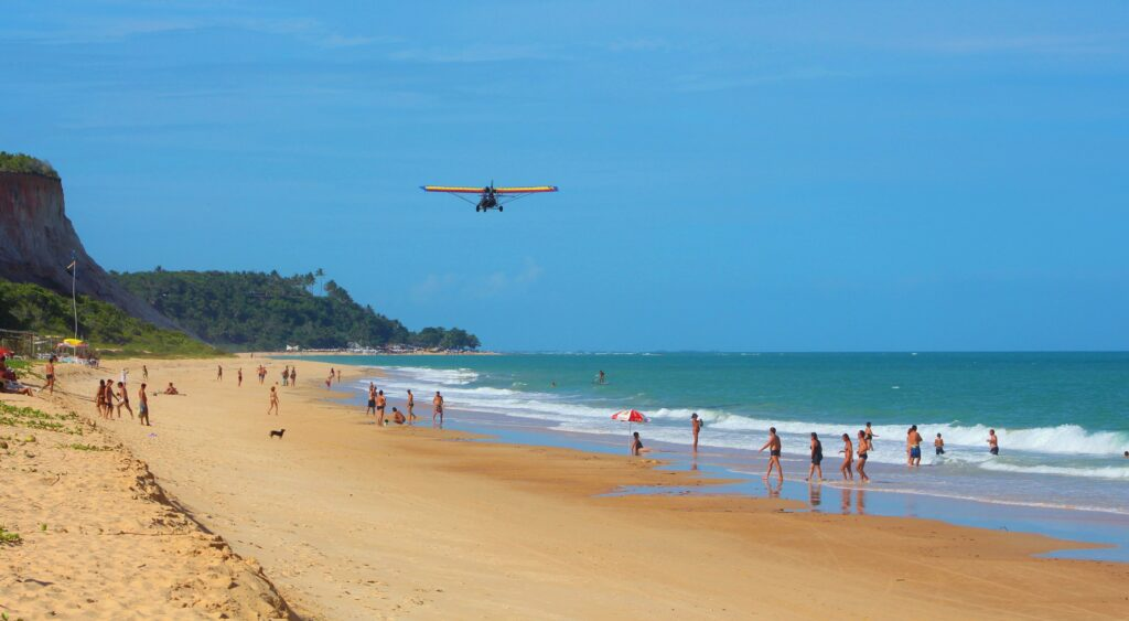 Pessoas na água e na areia da Praia de Taípe em Arraial d'Ajuda na Bahia