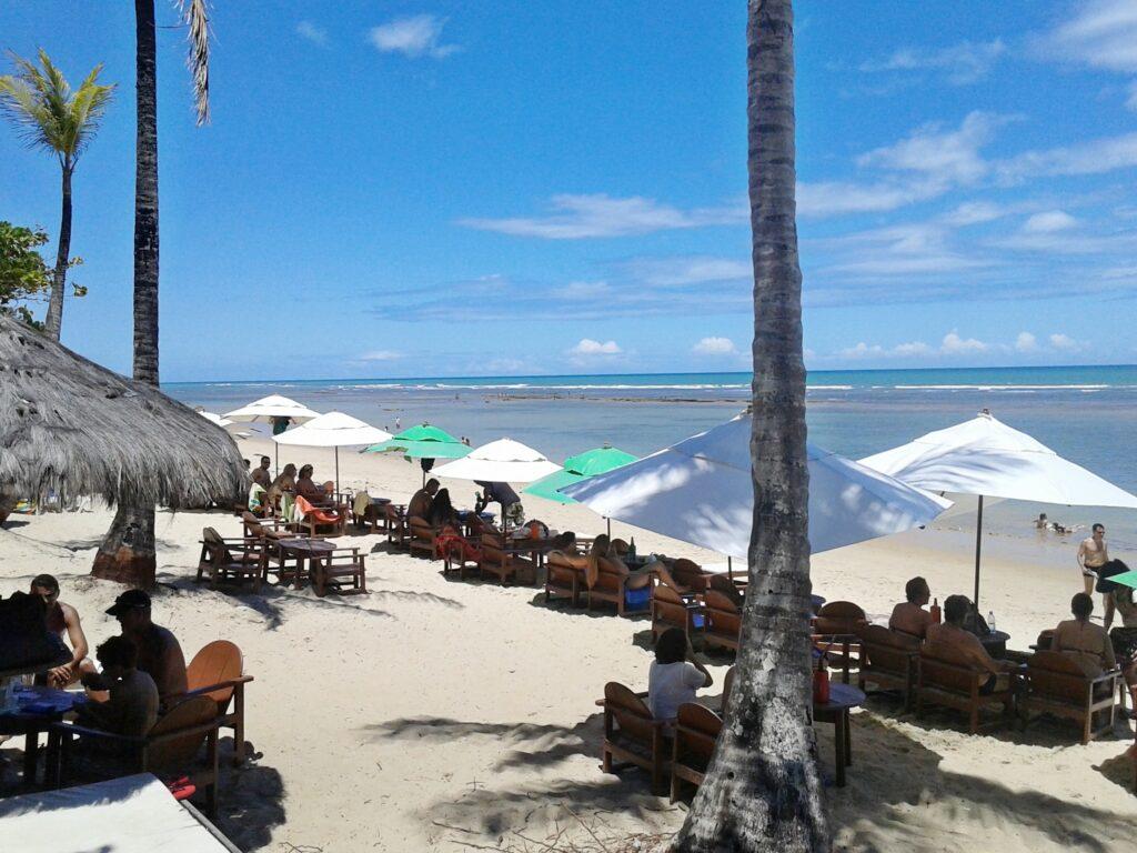 Pessoas sentadas embaixo do guarda-sol em frente ao mar de Praia do Mucugê em Arraial d'Ajuda na Bahia
