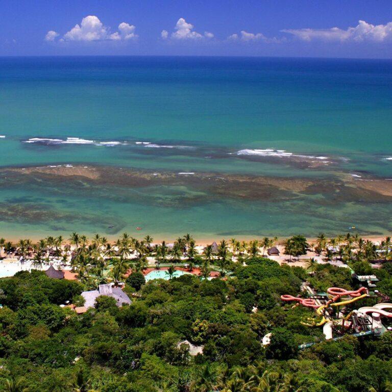 Visão de cima do Eco Parque Arraial d'ajuda com águas em tons de verde e azul, vegetação, tobogã e a piscina.