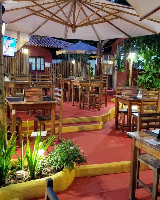 restaurante Boiteko com várias mesas de madeira sob um chão vermelho em Arraial d'Ajuda na Bahia