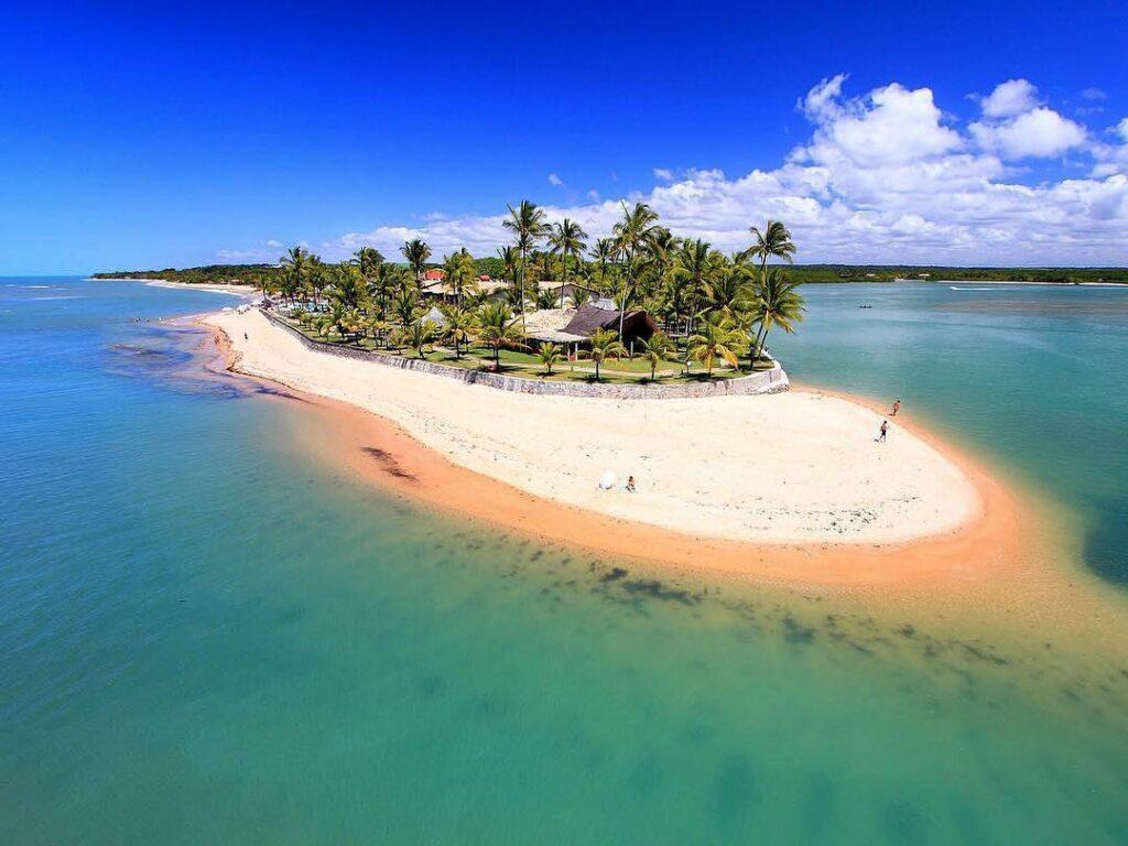 ilha com a água em tons de verde e azul o Arraial d'Ajuda Eco Resort no meio no Apaga-Fogo