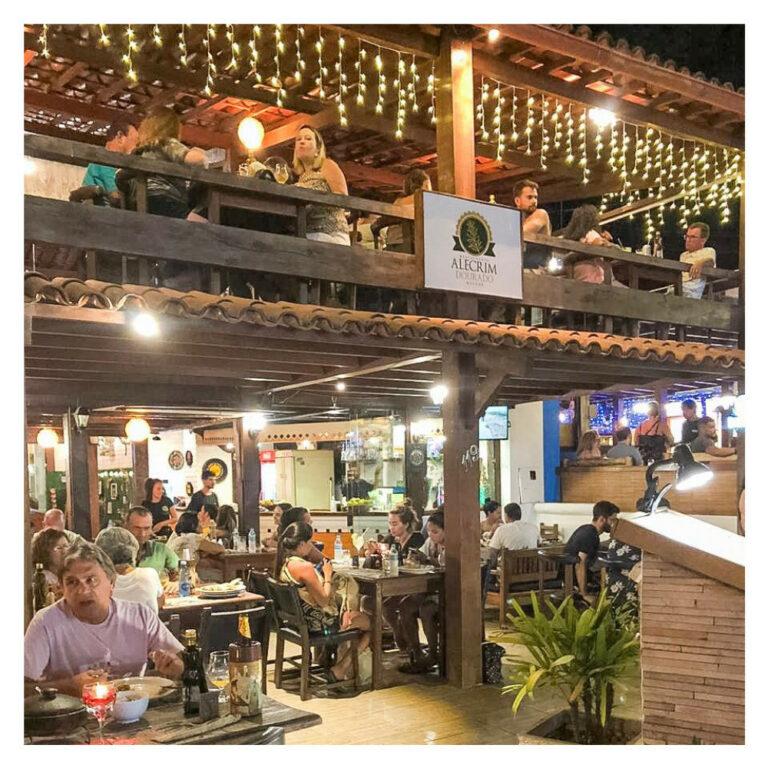 estabelecimento de dois andares com várias pessoas nas mesas interagindo no Restaurante Alecrim Dourado em Arraial d'Ajuda na Bahia