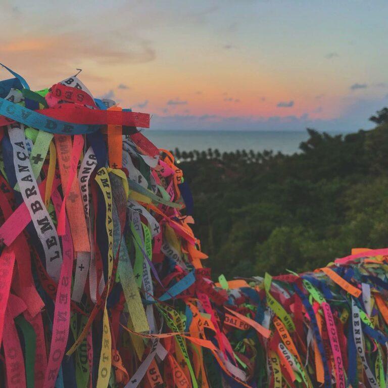 Várias fitinhas do Senhor do Bonfim amarradas em frente a um pôr do sol com uma vegetação do lado no Largo da Ajuda em Arraial d'Ajuda na Bahia