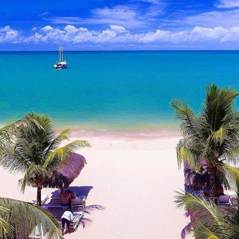 Mar azul piscina em frente a coqueiros e areia na Praia do Mutá em Porto Seguro na Bahia