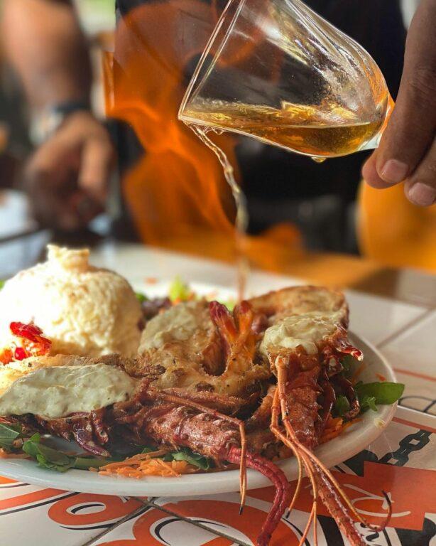 líquido avermelhado sendo derramado em cima da lagosta na Vovó Bela Restaurante em Porto Seguro na Bahia